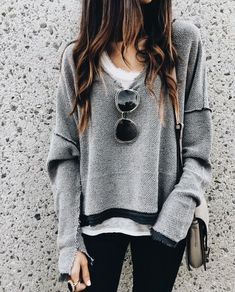 Casual gray sweater over white tee and black jeans.