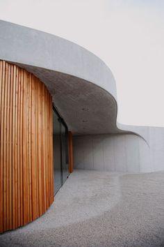 Curved, concrete chapel by OFIS Arhitekti nestles into the rising landscape