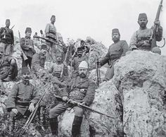 Most of these Ottoman soldiers in the mountains of Albania wear the M1909 uniform with the old-pattern red fez, but the bugler in the left background seems to have the old dark blue tunic. Interestingly, the Albanian irregular in the foreground, wearing a white skull cap and civilian clothing, has a certain air of authority about him. As a local pro-Ottoman Albanian leader he may have been given charge of this squad of regular soldiers.