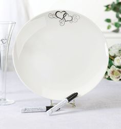 "Unik Occasions - Lillian Rose Round Silver Heart Guest Signing Plate with 2 Pens Remember those who shared the special events in your life with this ceramic keepsake signature plate -- a great alternative to guest books. This set includes one 12"" x 12"" ceramic plate and two food-safe ceramic pens for signing. Plate is dishwasher safe. At the top of the plate is a metallic silver design of double hearts and scrolls. Gold plate holder in photo not included.  Price $33.90"