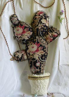 Lidée de réaliser un nouveau cactus pour Noël me titillait,mais je le voulais différent de mes cactées précédant.Jai donc décidé de mattaquer à une autre forme...Une fois la plante dessinée le choix du tissu sest porté sur ce tissu XIXeme ,un magnifique tissu fleuri sur fond noir aux fleurs exquises mêlées à des bijoux somptueux....Pour un cactus de NoËl il faut avouer que cest un peu la classe....Lidée de la fausse fourrure pour un cactus était évidente...;(blanche ancienne,très douce au…