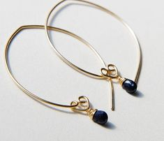 """A simplistic design that looks elegant and will stand the test of time. Blue sapphire teardrop sways delicately. These earrings were designed to transform easily from every day wear to just about any formal event you may need to attend. Total length of the earrings is 1.8"""" (4.5 cm), 20gauge ( 0.8mm thick) Sapphire 9mm ( includes a loop) Come in gift box Made to Order"""