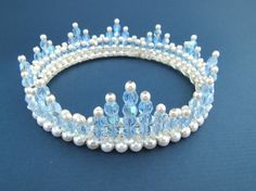 Created using blue crystal AB and 4mm white glass pearls attached to a tiara band. The crown measures 1.25 inches at its highest point.