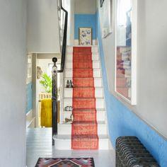 Pour mener à l'étage, l'escalier, typique des maisons victoriennes, est habillé d'un tapis rouge qui contraste avec la peinture bleue.
