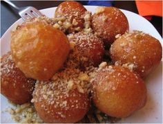 In Greece, loukoumades are commonly spiced with cinnamon in a honey syrup and can be sprinkled lightly with powdered sugar. In ancient Greece, these deep fried dough balls were served to the winners of the Greek Olympics. Greek Donuts, French Donuts, Greek Cookies, Greek Sweets, Greek Desserts, Greek Recipes, Fun Desserts, Beignets, Yummy Treats