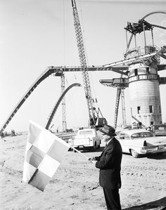 (1960)^* - LAX's Theme Building under construction in 1960. Airport Commission president Don Belding waves a flag in the foreground.