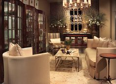This luxurious living space showcases a trio of the John-Richard Baraomda Bunching Curio Cabinets.