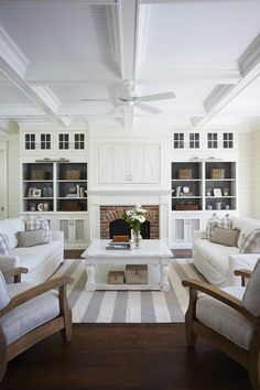 built-ins, fireplace, white color scheme, coffered ceilings, coastal stripe rug, slip covered sofas for nautical style