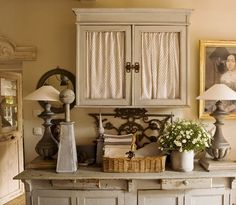 Curtains inside glass cupboard doors. Convenient solution for wanting an all-glass kitchen but needing to hide mess in some cupboards.