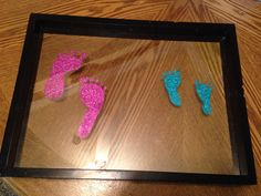 Glitter footprints on a floating glass frame. Use safe glue and rub it on child's feet, press onto glass and glitter. For permanent, use clear nail polish on top to seal the glitter in.