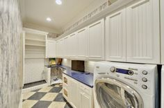 dream laundry room. Clean and white, subway tiles/backsplash, lots of space/storage, and area for dog with built-in doggie bath. Also good for very dirty children!