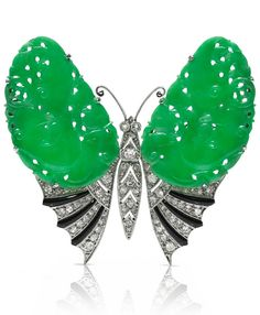 An Art Deco platinum, enamel, jade and diamond 'Butterfly' brooch, circa 1925. The finely carved butterfly with wings of fine jadeite, pierced and engraved, each measuring approximately 3.1 x 1.9cm, partially enamelled in black and set with diamonds. Brooch measurements 5 x 4.5cm. #ArtDeco #brooch