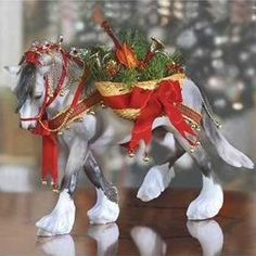 Breyer's 11th holiday horse is a dapple grey shire with feathers as white as freshly fallen snow. The silvery stars and red and gold tassels that bedeck his mane and tail glisten and the jingle of his Christmas bells proclaim his arrival. Clad in tartan harness, this gentle Shire carries on side a basket lined with greenery, filled with musical instruments, and laced with bows. usher in the joy of the season with Wintersong. Previsously offered in porcelain as Breyer's Drum Horse…