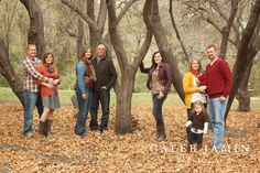 Family portrait in a field on a red couch photo shoot Fall family photo clothing ideas