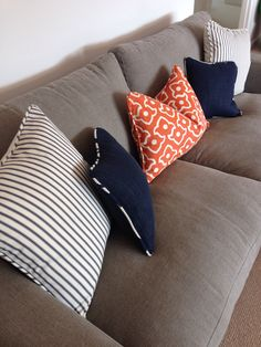 Living room neutral grey sofa with orange and navy cushions