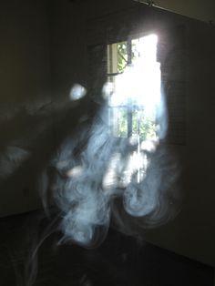 Beautiful luminous image of smoke swirling sensually in shafts of light through an old window.