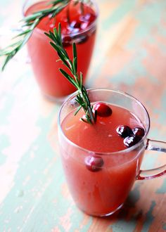 Slow Cooker Rosemary-Cranberry Mulled Cider - This Crock Pot spiced apple cider recipe gets its rosy glow - and an irresistible pop of flavor - from fresh cranberries. Rosemary adds an unexpected (and festive) vibe.