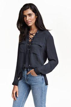 Blusa con lazada: Blusa en tejido vaporoso con cuello elevado con lazada, mangas largas, bolsillos superiores con solapa y aberturas en los laterales.