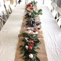 An Australian table runner made from native plants and flowers. Featuring a cake, plums, cherries, lamingtons and mini pavlovas on a teared cake stand. Perfect for Australia Day!