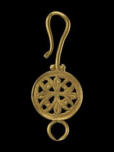 Necklace clasp; gold; composed of an open-work (opus interrasile) disc of gold sheet, decorated with a chased symmetrical foliate design; at opposite sides a fastening ring and long hook, whose joint to the central disc is partially masked by three gold granules.       Early Byzantine - 6thC-7thC. Gold