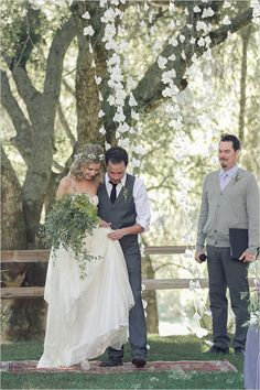 love the look of this outdoor wedding. simple bouquet of greenery, flowers in her hair and hanging from the trees, grooms wardrobe (and the officiant!!)