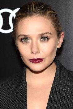 Who: Elizabeth Olsen  What: High Impact Makeup How-To: Dark red lips and glittery eyes don't look too done when paired with clean menswear lines and sleek, pulled-back hair. Focus the silver shadow at the inner corners to brighten your eyes, then smudge khol pencil along the top and bottom lashes.  Editor's Pick: Chanel Illusion D'Ombre Eyeshadow in Mysterio and Rouge Allure Lipstick in Pirate, $36 each, chanel.com.   - HarpersBAZAAR.com