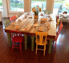 Dining room table with different chairs all fun colors