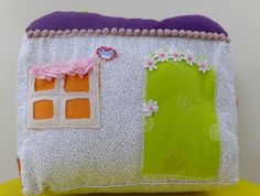Dinky Dollhouse Cushion.   Sweet child's cushion in the shape of house. Detailed appliqué and carry handle makes this cushion a sweet addition to any child's play and bedroom.  Filled with hypoallergenic filling. 11.5cm wide, 18cm long, 17cm high. Fully washable.