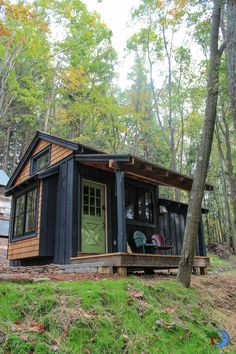 A natural stained board and baton were used as exterior trim and cedar decking boards were used for the entrance porch. This rustic cabin is available to rent. | Tiny Homes