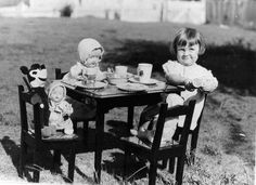 Young girl entertaining Mickey Mouse and other friends at a make-believe tea party, 1930s by State Library of Queensland, Australia, via Flickr