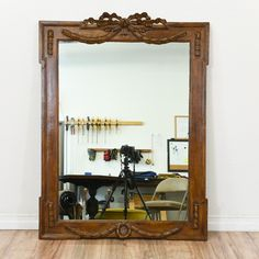 This mirror is featured in a solid wood with a glossy walnut finish. This accent mirror is in good condition with intricate carved trim, ribbon and swag accents. Perfect for accenting a wall! #americanmidcentury #decor #mirror #sandiegovintage #vintagefurniture