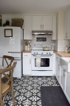 White Kitchen remodel with patterned tile and butcher block counter tops. Retro oven and fridge.