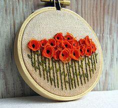 tangerine poppy art in embroidery hoop.