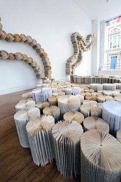 """Yvette Hawkins creates large-scale book art installations. For the installation """"No Land in Particular"""" (see images above) the artist laid a cluster of books on the floor, resembling an organic land mass, which upon meeting the walls climbed up and out tracing a snail-like path."""