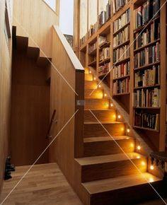 Bücherregal über beleuchteten Stufen im Treppenaufgang eines Holzhauses