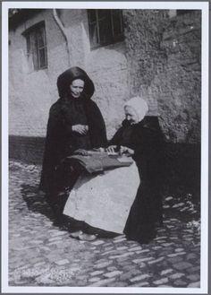 De vrouw rechts is een kantwerkster. Bemerk het kantkussen en haar kapmantel en pijpemuts. Brugge