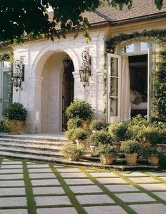 Mediterranean Style front entryway with wrought-iron lanterns. I also love the grass between each stone pavement