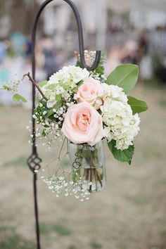 Line your wedding aisle with flowers in glass jars so a sweet touch. Featured Photographer: Larissa Nicole Photography via Bridal Musings