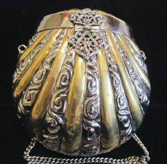 This is a pretty vintage 1930's silver and brass shell pillow purse or handbag. It has a silver exterior with some brass accents, and is decorated with an gorgeous clasp and hinge.