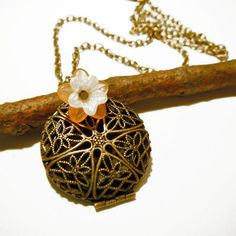 "Filigree Locket Necklace  by Britt Baker (""Dainty and feminine with oodles of vintage charm, this necklace features a bronze-tone round filigree locket on a long antiqued brass chain. A soft orange Lucite daisy with a white pearl center atop the pendant finishes off the look."")"