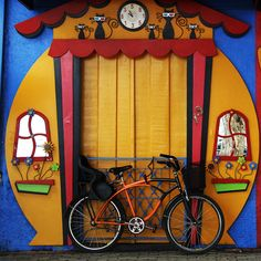 This doorway in Brazil is hilariously cute. Fake windows and flowers, painted clock and cats, great colors, what a whimsy.