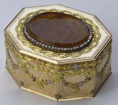 Faberge Patchbox, Patch box   Creator:  Mikhail Evlampievich Perkhin (1860-1903) (workmaster) Creation Date:  1894 Materials:  Four-colour gold set with moss agate and rose cut diamonds    Provenance:  Presented to Queen Mary when Duchess of York by Tsar Nicholas II and Tsarina Alexandra Feodorovna, Christmas 1894 Description:   Mark of Michael Perchin; gold mark of 56 zolotniks (before 1896); Fabergé in Cyrillic characters.