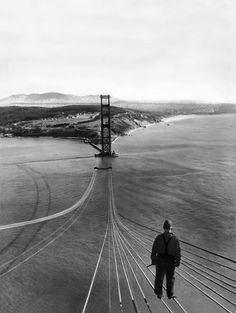 A man stands on cables over the Golden Gate Bridge, circa 1933. via http://gizmodo.com/20-photos-of-iconic-buildings-and-bridges-as-they-were-514156622