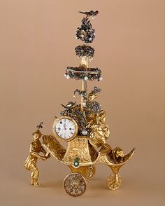 Automaton in the form of a chariot pushed by a Chinese attendant and set with a clock. James Cox.1766. London. Case: gold, with diamonds and paste jewels set in silver, and pearls; Dial: while enamel; Movement: brass, partly gilded, and steel, wheel balance and cock of silver set with paste jewels