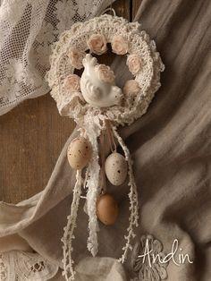 Velikonoční věneček shabby chic Romantický velikonoční krajkový věnec shabby chic, na dveře nebo do okna, na poličku. Jemné pudrové barvy, smetanová a broskvová. Krajková mašlička je zdobena shabby keramickou slepičkou a třemi vajíčky v jemných přírodních barvách. Poutko pro zavěšení, Průměr věnečku 11 cm, délka závěsu s vajíčky 13 cm