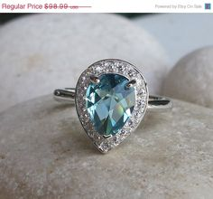 A lovely Pear Shaped London Blue Quartz Halo Ring encrusted with pave set white crystal in Sterling Silver. It the perfect halo ring for that special