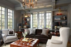 Incredible den with smoky gray painted wood paneled walls, built-in bookcases flanking windows and millwork ceiling. A dark brown velvet sofa with gray pillows sits in front of the bookcase wall with a pair of traditional round side tables at either end topped with silver trophy table lamps.