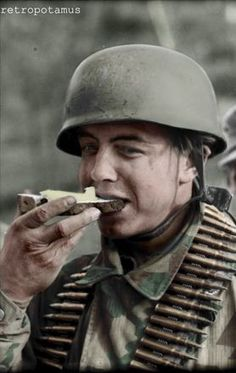 A German paratrooper enjoys a slice of buttered bread, 1944, France.  Colorized by Retropotamus. -