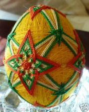 Temari Egg made from Orange White and Green thread over a Bright Yellow Base