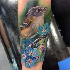Gorgeous realistic little bird with blue and purple flowers tattoo by Jesse Rix